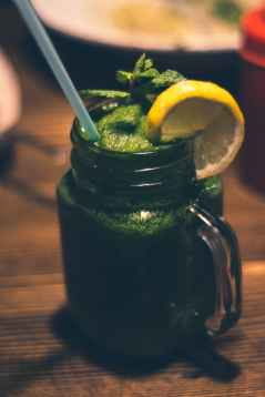 close up photography of clear glass mason jar mug with green juice and sliced citrus toppings